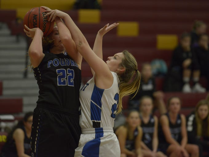 Poudre's Elsa Berkner is fouled while driving to the