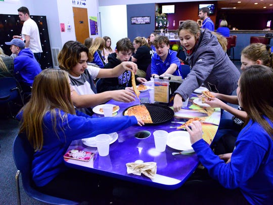 Members of Put-in-Bay Schools' co-ed junior high and varsity basketball teams enjoy pizza after playing St. Joseph's Central Catholic in Fremont on Thursday. After the meal they boarded a bus and headed to a hotel in Port Clinton before flying back to school on Friday morning.
