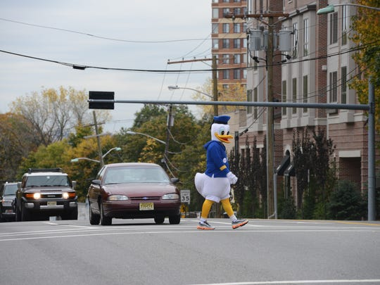 In this on Friday, Oct. 31, 2014 file photo, Detective Edward Young, dressed as a duck, serves as a decoy for drivers who fail to stop for pedestrians on Hudson Terrace in Fort Lee.