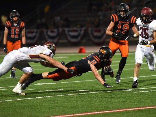 Washington High School Jhett Andersen (12) dives with