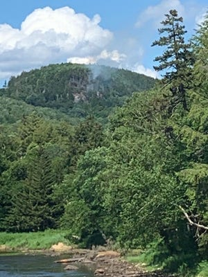 Smoke can be seen coming from the side of Panther Mountain, in Old Forge, Thursday afternoon. Fire officials were able to contain the fire that burned approximately 10 acres of land.