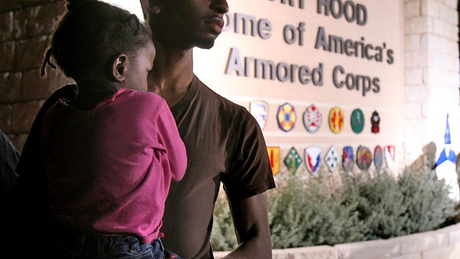 Spc. Jerry Richard and his daughter Samyia Jones, 3, wait outside of the main gate to Fort Hood in Killeen in 2009. The Pentagon is considering renaming 10 U.S. Army posts named for Confederate generals, including Fort Hood.