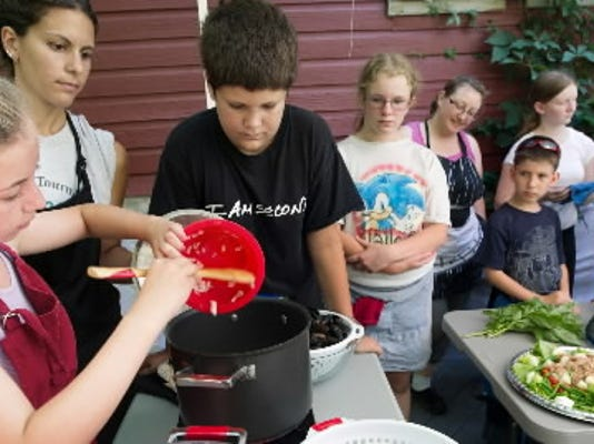 Arielle Lebouitz, age 11, of Dallastown, pours her onions into the Mussels Provencal that the red group is making during the Teen Battle Chef program at Sproutwood Farm in Codorus Township July 15, 2013. YORK DAILY RECORD/SUNDAY NEWS - PAUL KUEHNEL