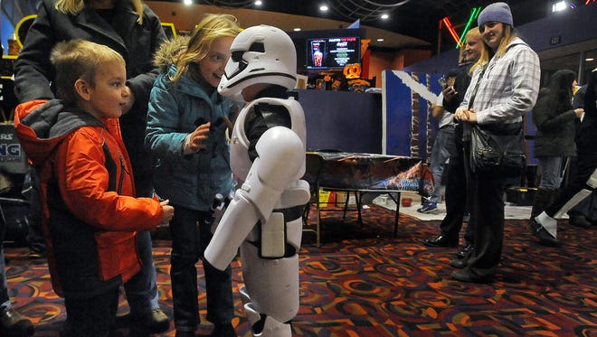 Thomas (left) and Kaija Borgmann examine their friend Dominic Downs, 6, in his Stormtrooper costume made by his father, Brian, before the first showing of Star Wars: The Force Awakens on Thursday, Dec. 17, 2015.