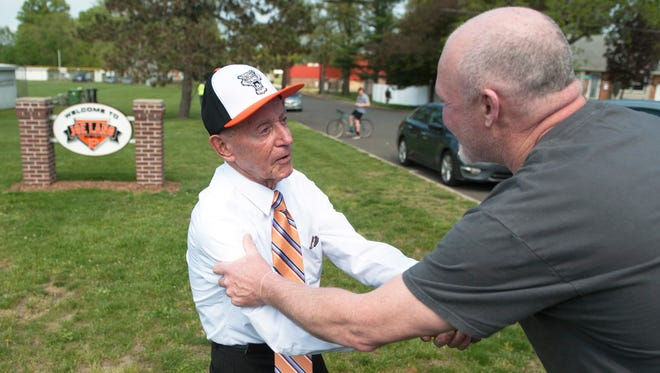 Former Pitman High School baseball coach Joe Lang. left, is congratulated by former Pitman pitcher John Milward after the unveiling of the new sign at Pitman High School baseball field which is dedicated to Lang.