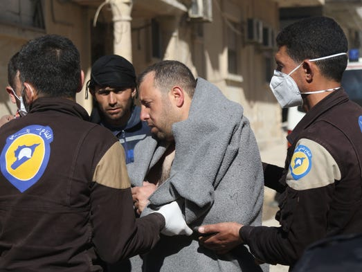 A Syrian man is taken by civil defense workers to a