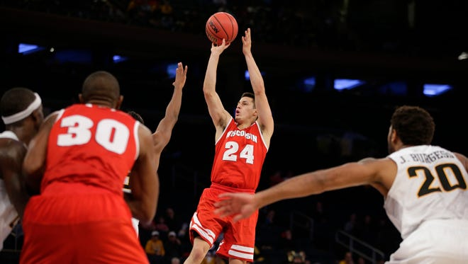 Wisconsin guard Bronson Koenig (24) shoots as Virginia Commonwealth guard Jordan Burgess (20)  defends and Wisconsin forward Vitto Brown (30) watches in the second half of the third-place game in the 2K Classic in New York.