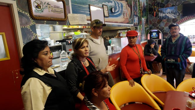 King City residents gather at the restaurant of Veronica Villa, center, with red apron, to discuss a police car theft ring on Wednesday, Feb. 26, 2014, in King City, Calif.