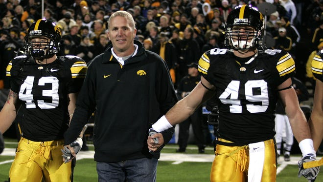 Former Iowa quarterback Chuck Long, center, serves as honorary captain and walks for the coin toss before a game against Michigan in 2009.