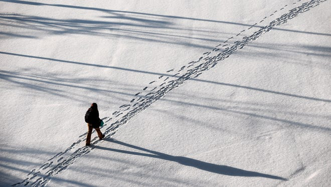 People cross through a fresh layer of snow and footsteps in the parking lot of the Indianapolis Star on Monday, February 3, 2014. More snow is in the forecast for this week.