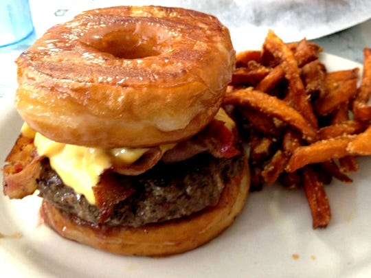 The popular Donut Burger has a meat patty with bacon and American cheese between two glazed doughnuts at Brook's Gourmet Burgers & Dogs in Naples.