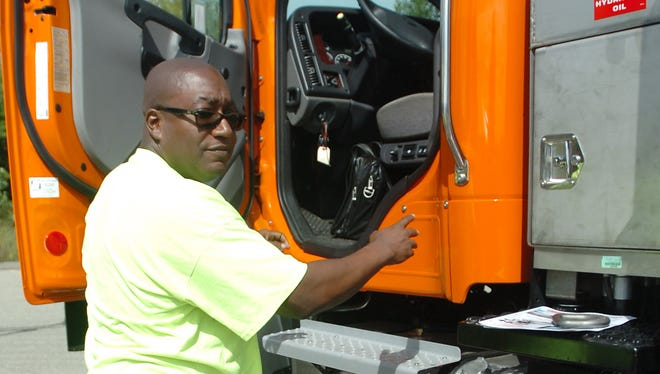 Farmington driver Kelvin Robinson climbs in a plow truck at the regional skills contest held at the Palace of Auburn Hills.