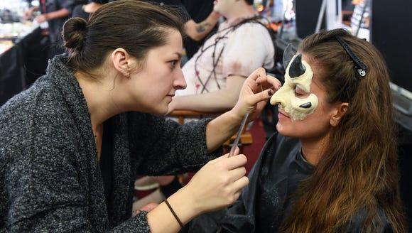 Special effects makeup artist Miranda Jory applies