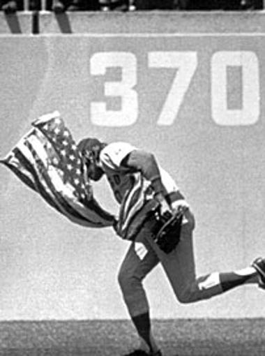 Outfielder Rick Monday of the Chicago Cubs dashes between two men in the Dodger Stadium outfield in Los Angeles, in this April 25, 1976 photo, snatching an American flag the men were about to burn.