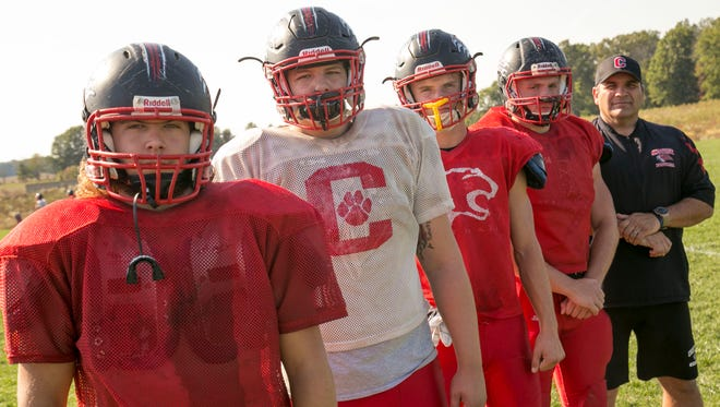 Crestview football seniors (left to right) Shane Casper, Dakota Slocum, Dawson LeFever and Chandler Prise stand with  head coach Dan Mager during practice Wednesday afternoon.