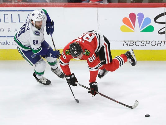 Chicago Blackhawks' Patrick Kane (88) falls to the ice as Kane and Vancouver Canucks' Sam Gagner chase a loose puck during the first period of an NHL hockey game Thursday, March 22, 2018, in Chicago. (AP Photo/Charles Rex Arbogast)