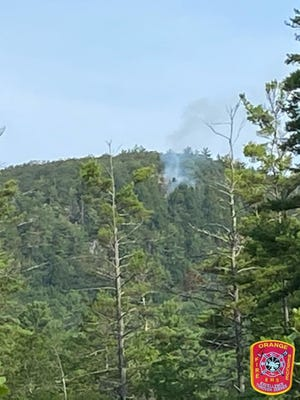 Firefighters summoned a National Guard helicopter on Tuesday to help attack a brush fire on Tully Mountain in Orange.
