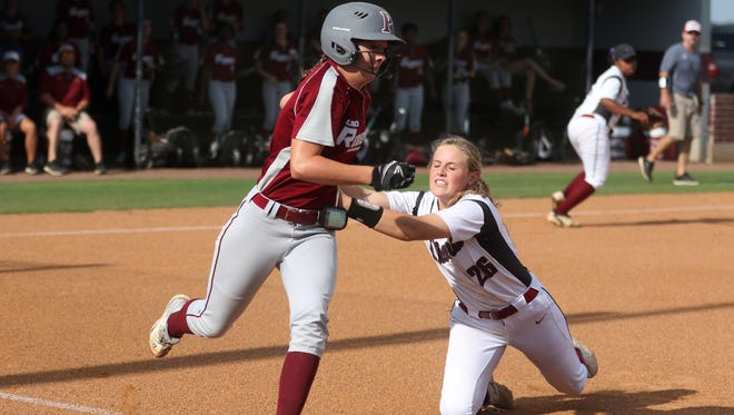 Ouachita's Jordyn Manning tries to defend first base as Pineville's Abbriel Robertson runs to first base in the round 2, Class 5A softball playoffs at Ouachita High School in Monroe, Friday, April 21, 2017. Ouachita beat Pineville 6-1.