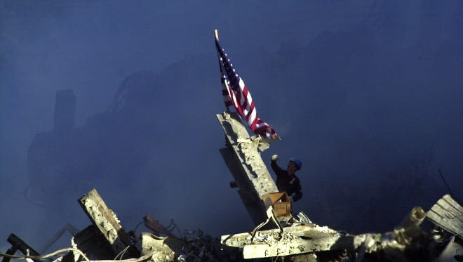 A rescuer reaches up to untangle an American Flag on top of the rubble of the World Trade Center towers on Sept. 13, 2001.