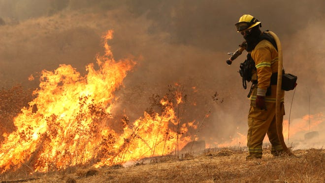 Firefighters work to protect homes along Bennett Valley Road east of Santa Rosa, Calif., Oct.11, 2017.