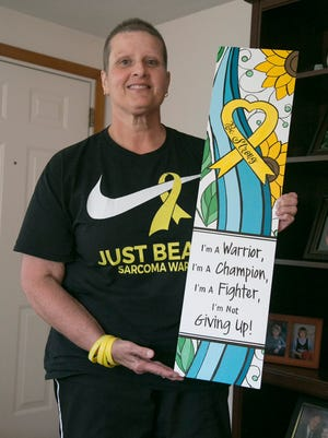 Jean Newmeyer holds a painting done by a fellow Indian Lake Middle School teacher. The yellow ribbon and the sunflower represent sarcoma, which Jean has been battling for over a year, but she has been cleared to return to teaching. She has been staying in Shelby with her parents.