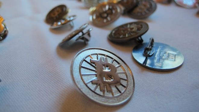 Bitcoin buttons are displayed Feb. 12 on a table at the Inside Bitcoins conference in Berlin.