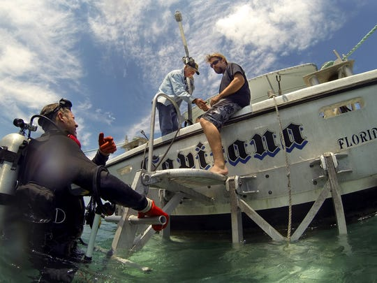 William Bartlett (left) speaks with Jonah Martinez (right) and Doug Kaye between dives while treasure hunting aboard the Capitana near Wabasso in 2014.