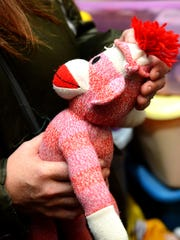 Stephanie Jezowski holds a sock monkey that belonged