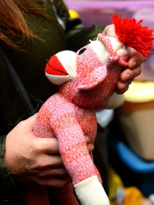 Stephanie Jezowski holds a sock monkey that belonged to one of her daughters. She and her husband, Ted, lost their parental rights in court in 2014. They still keep many of their kids' articles of clothing and toys.