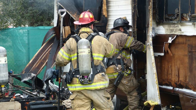 Firefighters enter the still smoldering RV as they begin to mop up.