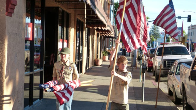 A portion of Market Street was red, white and blue Wednesday morning as Redding Boy Scout Troop 37 posted flags there Wednesday to celebrate Flag Day. Shown, left to right, are Daniel Snider and Ethan Borland.