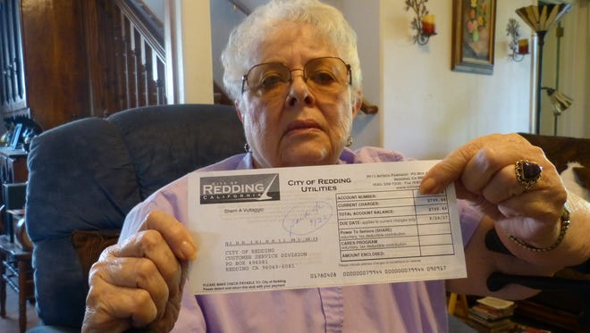 Sherri Vultaggio displays her $799 REU bill Tuesday at her Country Heights home.