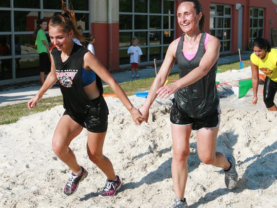 Angi Dimmitt, right and Hillary Hospodar hold hands as they approach the finish line while competing in the Gruesome Twosome Challenge organized by the Bonita Springs YMCA on Saturday. The 3-mile run included an obstacle course with cargo net walls, a balance beam, wall climb, inflatable slide and many other obstacles ending with a mud pit.