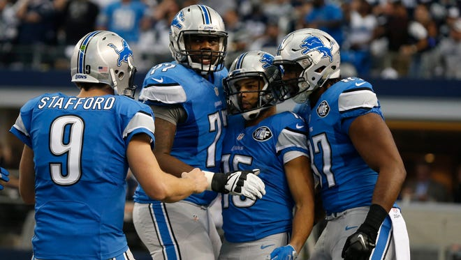 Jan 4, 2015; Arlington, TX, USA; Detroit Lions wide receiver Golden Tate (15) celebrates his touchdown pass with Matthew Stafford (9), Cornelius Lucas (77) and Brandon Pettigrew (87) against the Dallas Cowboys  during the first quarter in the NFC Wild Card Playoff Game at AT&T Stadium.