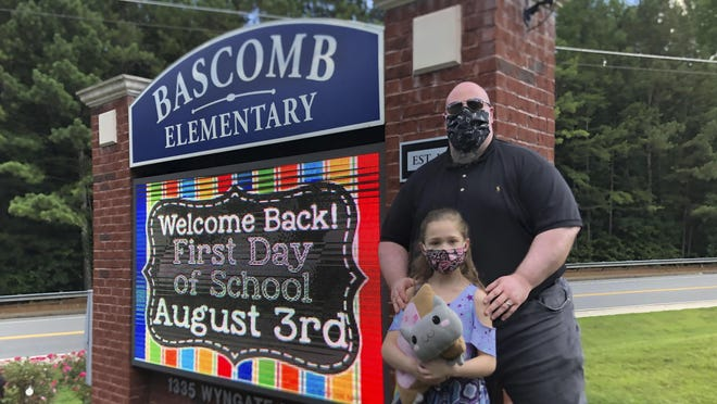 John Barrett and his daughter Autumn pose for photos outside Bascomb Elementary School in Woodstock, GA, Thursday, July 23, 2020. Barrett says he will educate his daughter virtually and keep her out of in-person classes in Cherokee County schools, even though he's worried she will fall behind on her special education plans, because of concerns about COVID-19's spread. Cherokee County, near Atlanta, is one of many districts nationwide that gave parents a choice between in-person and all-online classes this fall.
