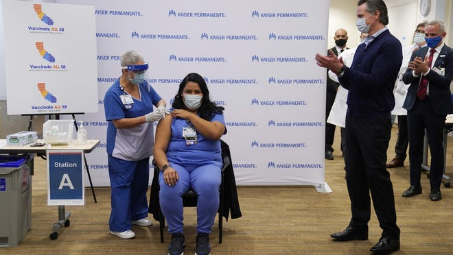 California Gov. Gavin Newsom, at right, watches as ICU nurse Helen Cordova receives the Pfizer-BioNTech COVID-19 vaccine at Kaiser Permanente Los Angeles Medical Center on Monday.