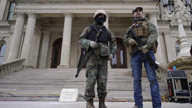 Men with a shotgun and a rifle stand on the steps at the state capitol after a rally in support of President Donald Trump in Lansing, Mich., Wednesday, Jan. 6, 2021.