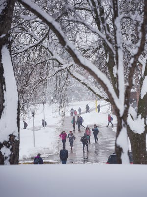 Augustana students make their way around campus in the snow Wednesday, April 18, at the university in Sioux Falls. Sioux Falls received 6.2 inches by 11 a.m. according to the National Weather Service.