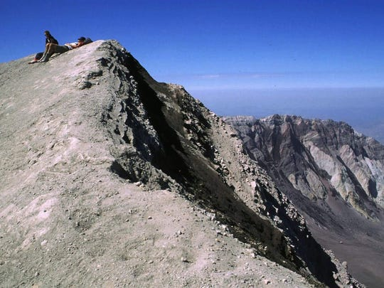 Climbers rest on the summit of Mount St. Helens on the south side of the mountain, which is still open to climbers from the public who get a permit.