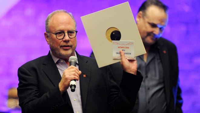 Mike Dungan helps auction off an autographed Paul Simon album during a Phil Everly benefit concert.
