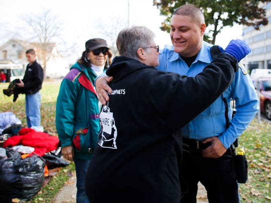 Cardboard Prophets volunteer Linda Karl of Eaton Rapids hugs Lansing Police Department Officer Tony Rodriguez, Tuesday, Nov. 14, 2017, at Reutter Park in downtown Lansing.  Rodriguez helped facilitate parking for the organization's ARK, or Act of Random Kindness mobile home parked on East Lenawee Street that carries supplies and donations for the community.  The organization set up tables with water and snacks, and brought boxes of winter clothing to give to those in need.  They are stationed on the southwest corner of the park each Tuesday and Wednesday between 11 a.m. and 2 p.m.