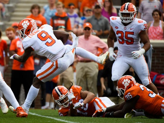 Clemson running back Travis Etienne (9) jumps over