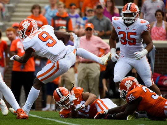 Clemson running back Travis Etienne (9) jumps over linebacker Judah Davis (36) during the 2018 spring football game on Saturday, April 14, 2018.