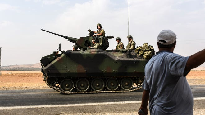 A Turkish man stands as a Turkish tank convoy drives to Syria from the Turkish Syrian border city of Karkamis in the southern region of Gaziantep, on August 26, 2016.