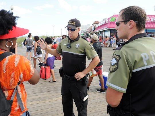 (L-R) Rehoboth Beach Police Officers Joshua Ream and Brian Reynolds give a visitor directions as crowds are in town on a Saturday evening in downtown Rehoboth Beach.