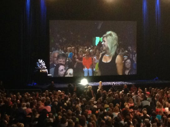 Theresa Caputo addresses an audience member as a spirit