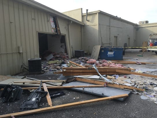 Debris from inside Advance Tax Services is strewn behind