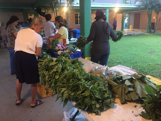 Shoppers peruse local fresh produce at the Agat Night
