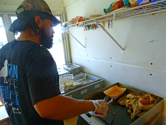 Apollo Burel cooks chicken and pulled pork for an order.