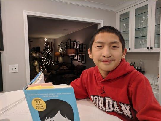 "Luke Canna reading ""Wonder"" by R.J. Palacio in his"